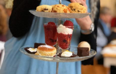 Three tier stand filled with a delicious selection of mini scones, sweet treats and finger sandwiches.